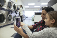Mother and daughter using digital tablet, waiting for laundry at laundromat - HEROF19055