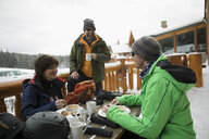 Mature skier friends enjoying coffee and lunch apres-ski on ski resort balcony - HEROF19061