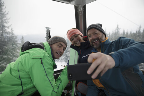 Mature skier friends riding gondola, taking selfie - HEROF19067