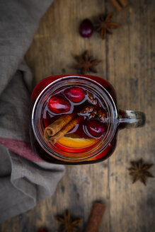 Glass of mulled wine with cranberries, cinnamon sticks, orange and star anise on dark wood, focus on foreground - LVF07759