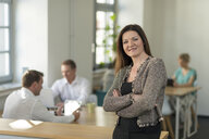 Portrait of smiling businesswoman in office with colleagues in background - PAF01862