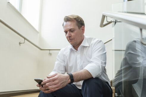Businessman sitting in staircase using cell phone - PAF01874