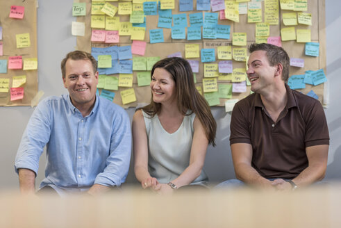 Smiling colleagues sitting in front of wall with sticky notes in office - PAF01886