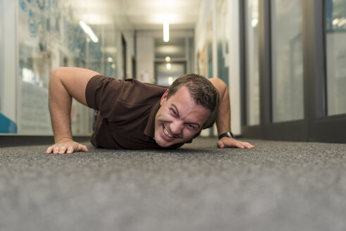 Businessman doing push-ups on office floor - PAF01910