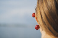 Back view of young woman wearing cherries on ear, close-up - JSCF00138