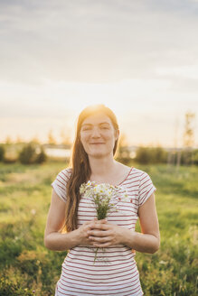 Portrait of smiling young woman holding bunch of picked wildflowers at sunset - JSCF00144