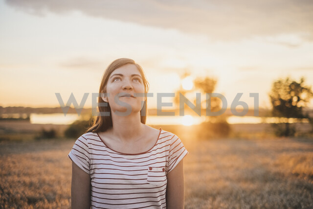 Portrait of young woman relaxing in nature at sunset - JSCF00150