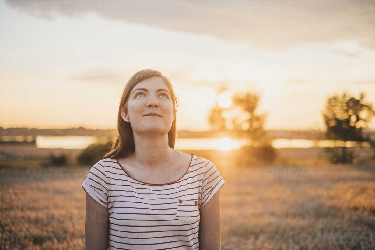 Portrait of young woman relaxing in nature at sunset - JSCF00150 - Jonathan Schöps/Westend61