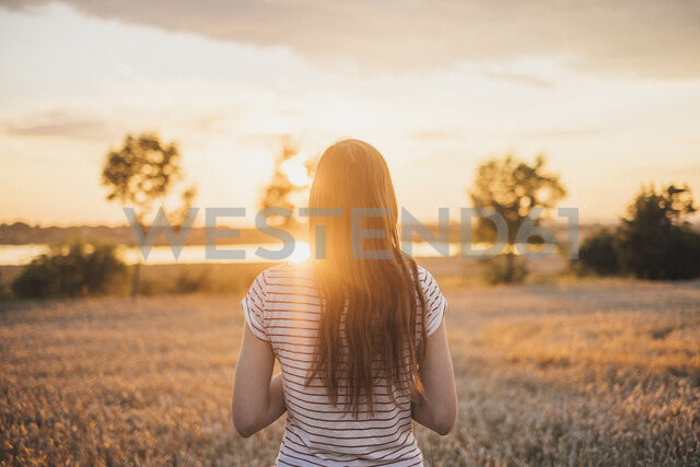 Back view of young woman watching sunset - JSCF00153