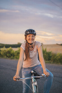 Portrait of smiling young woman with bicycle on a country road at evening twilight - JSCF00156