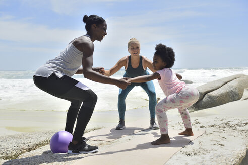 Mother with daughter and friend doing a fitness exercise on the beach - ECPF00383