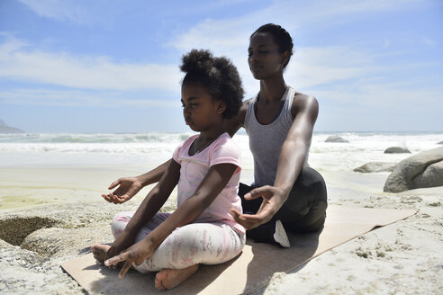 Mother with daughter doing a yoga exercise on the beach - ECPF00395