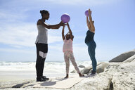 Mother with daughter and friend exercising with a ball on the beach - ECPF00401