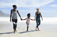 Happy mother with daughter and friend walking on the beach - ECPF00413