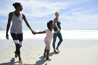 Happy mother with daughter and friend walking on the beach - ECPF00416