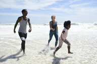 Mother with daughter and friend having fun in surf on the beach - ECPF00419