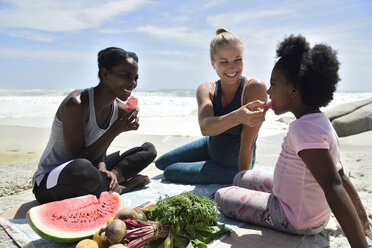 Mother with daughter and friend having a picnic on the beach - ECPF00422