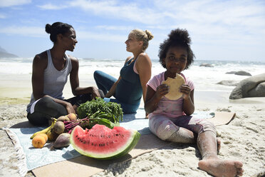 Mother with daughter and friend having a picnic on the beach - ECPF00425