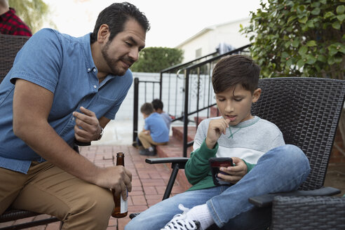Latinx father and watching son with smart phone on patio - HEROF19111