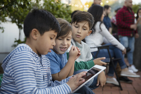 Latinx boys using digital tablet on patio - HEROF19150