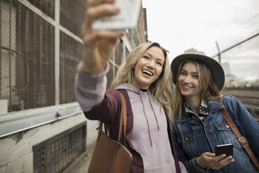 Enthusiastic young women friends taking selfie with camera phone - HEROF19415