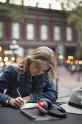 Blonde young woman writing in journal at sidewalk cafe - HEROF19418