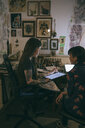 Client watching tattoo artist sketching tattoo on digital tablet - HEROF19493