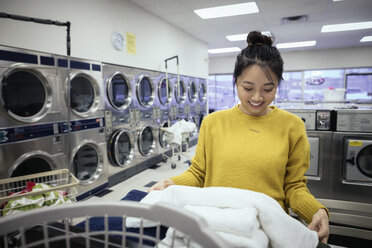 Smiling young woman folding towels, doing laundry at laundromat - HEROF19607