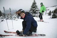 Portrait smiling, enthusiastic mature female skier preparing skis in snow - HEROF19655