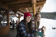 Smiling young female friends drinking beer apres-ski on snowy ski resort lodge balcony - HEROF19658