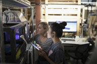 Female engineers using 3D printer and digital tablet in workshop - HEROF19679