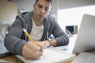 Focused creative businessman writing in notebook at laptop - HEROF19712