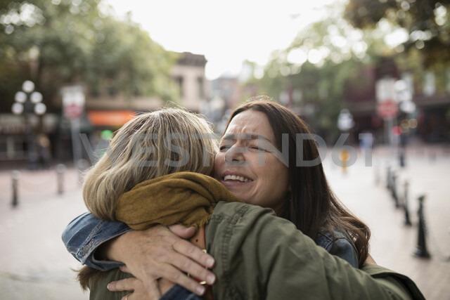 Happy mature women friends hugging on sidewalk - HEROF19715