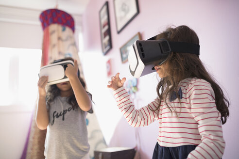 Girl sisters playing with virtual reality simulator glasses in bedroom - HEROF19724