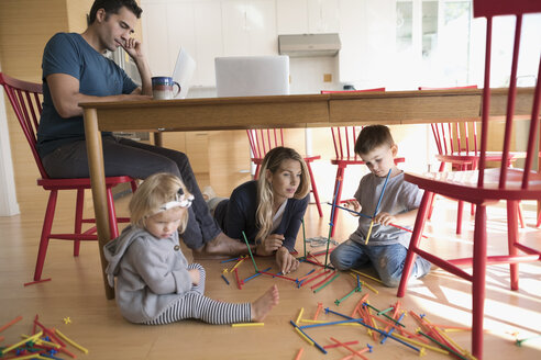 Father working at laptop at table and mother with toddler children playing with connector sticks on floor - HEROF19730