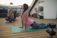 Female yoga instructor with video camera filming, vlogging upward facing dog yoga pose on patio deck - HEROF19739
