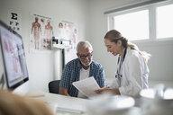 Female doctor explaining paperwork to senior male patient in examination room - HEROF19751