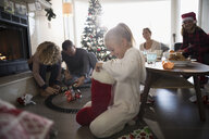Girl in pajamas opening Christmas stocking with family in living room - HEROF19772