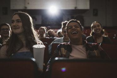 Laughing tweens watching movie in dark movie theater - HEROF19784