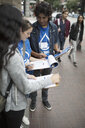 Political young adults canvassing with petitions on urban sidewalk - HEROF19835