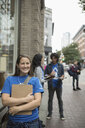 Portrait smiling, confident political young woman canvassing with clipboard on urban sidewalk - HEROF19838