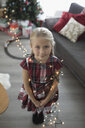 Portrait cute girl wrapped in Christmas tree string lights in living room - HEROF19889