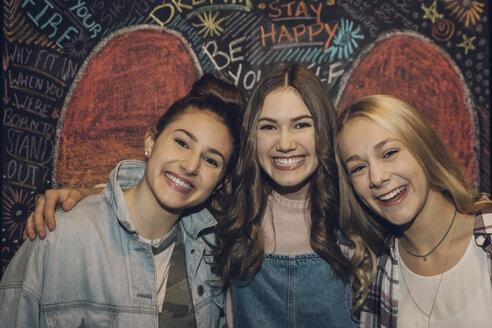 Portrait smiling, enthusiastic Caucasian tween girl friends against chalk wall - HEROF19892