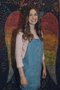 Portrait smiling, confident Caucasian brunette tween girl against wall with chalk wings - HEROF19895