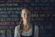 Portrait confident Caucasian tween girl with braid against wall with chalk text - HEROF19901