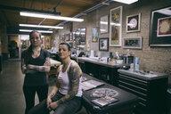 Portrait confident tattoo artists in tattoo studio - HEROF19919