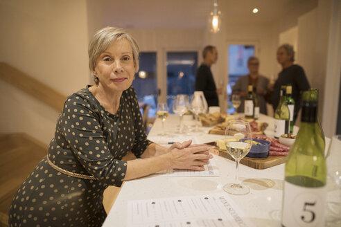 Portrait confident senior woman rating white wine at wine tasting party - HEROF19937