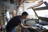 Male engineer using laser cutter in workshop - HEROF19943