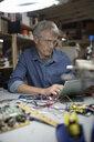 Male engineer using digital tablet at workbench in workshop - HEROF19949