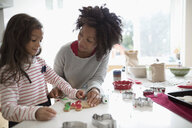 Mother and daughter decorating Christmas gingerbread cookies in kitchen - HEROF20003
